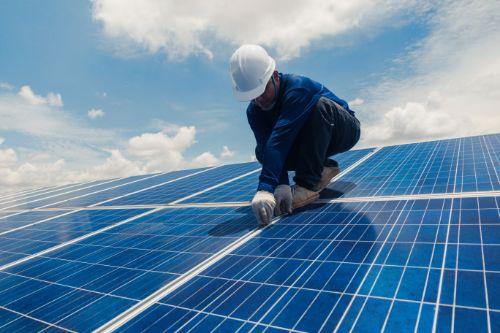 worker installing solar roof panels